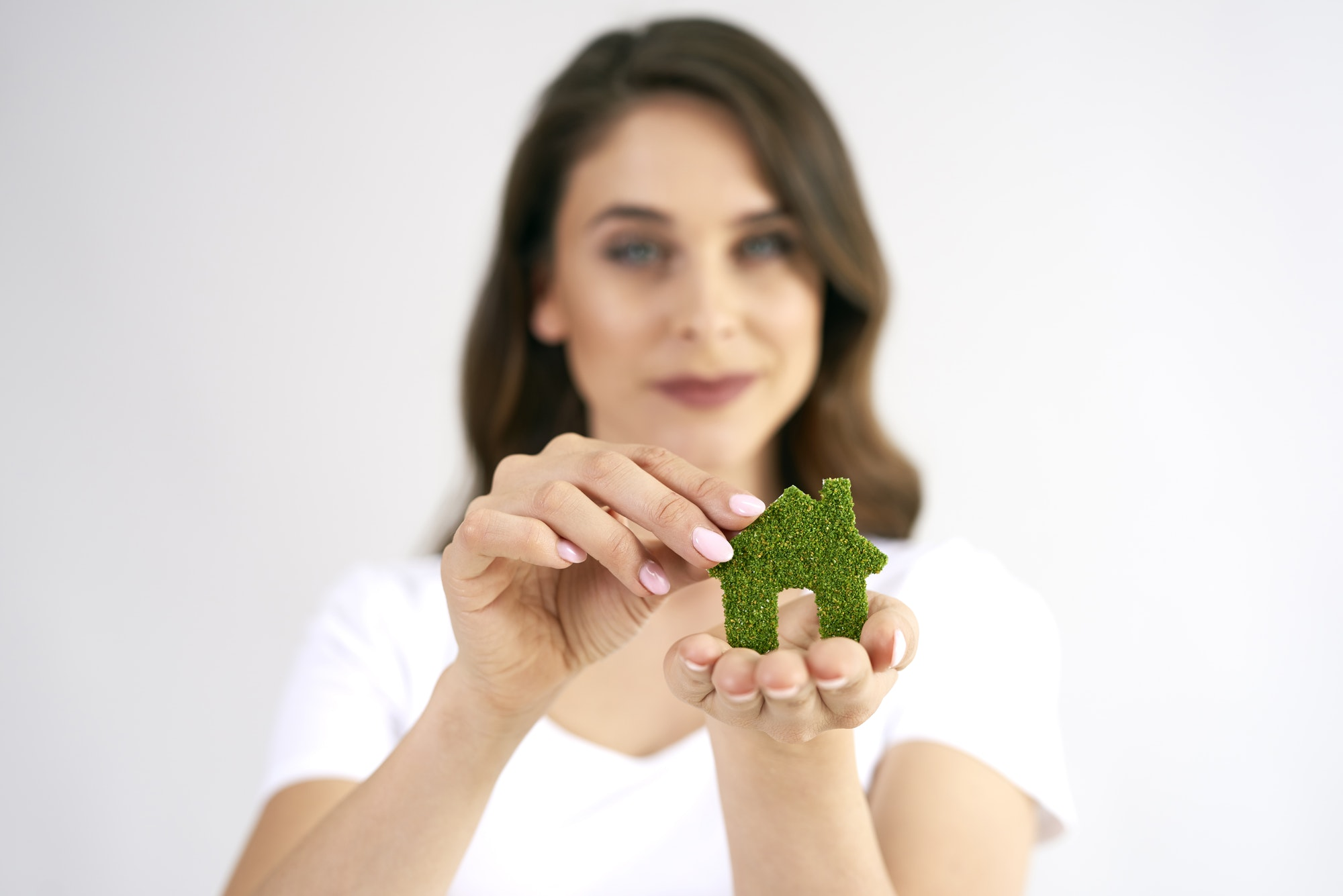 Woman's hand holding eco house icon